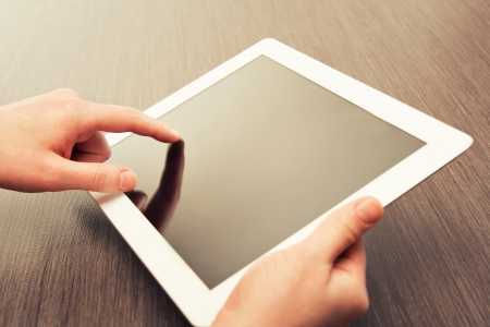 electronic tablet: white tablet with a  blank screen in the hands on wooden table