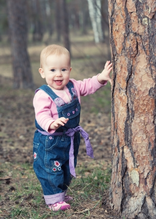 happy baby girl in jeans jumpsuit stands on legs near a tree in the park outdoors photo