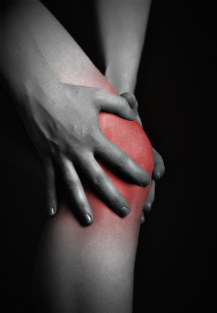 pain in the knee. Chiropractor doing massage in sick knee in black red color photo
