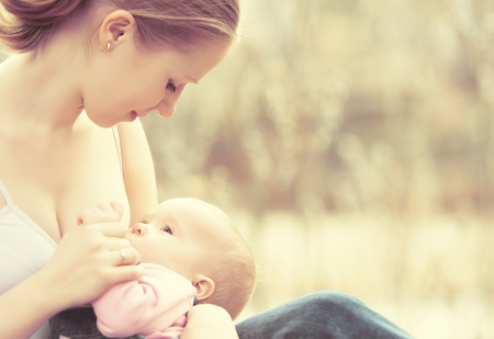 breasts girl: breastfeeding. mother feeding her baby in nature outdoors in the park