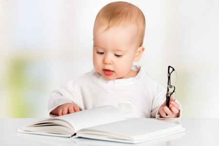 funny baby with glasses reading a book photo