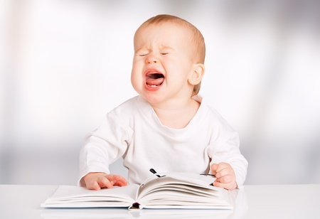 cries: funny baby with glasses reading a book and cries
