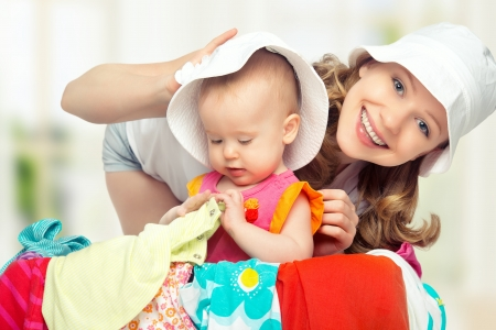 Mom and baby girl with suitcase baggage and clothes ready for traveling on vacation photo