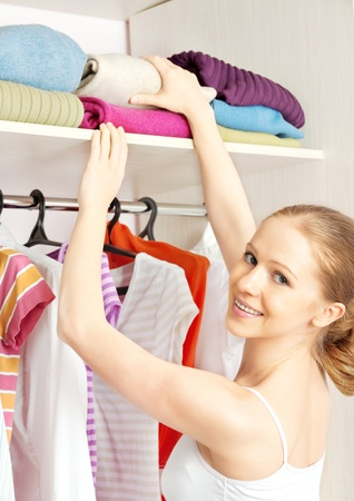 Young woman chooses clothes in the wardrobe closet at home photo
