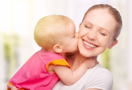 Happy cheerful family. Mother and baby kissing, laughing and hugging Stock Photo