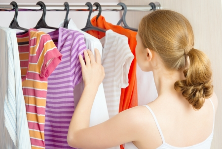 woman closet: Young woman chooses clothes in the wardrobe closet at home