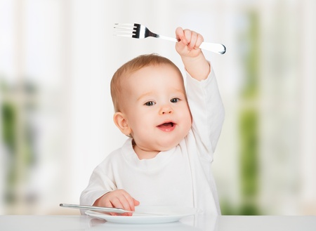 Funny happy baby with a knife and fork eating food photo