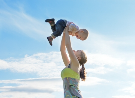 parenting: Mother throws up  baby in the sky in nature