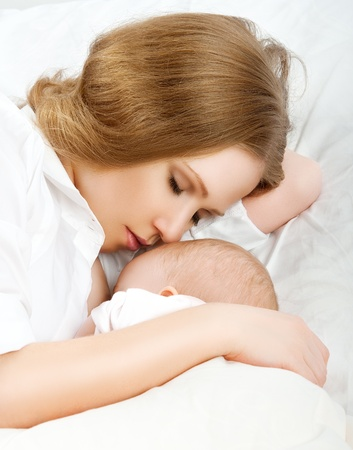 breasts girl: mother feeding breast her baby in the bed. sleeping together