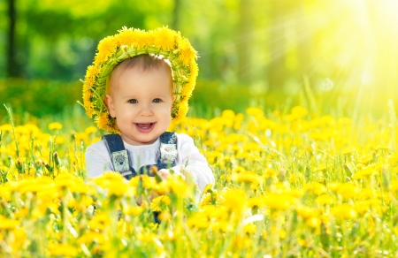Beautiful happy little baby girl in a wreath  on a  meadow with yellow flowers dandelions on the nature in the park