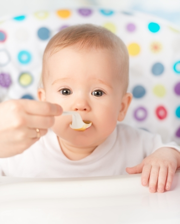 feed: Mother feeds funny baby from a spoon
