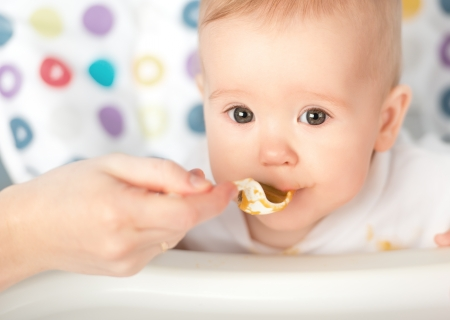 capricious: Mother feeds funny baby from a spoon