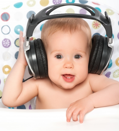 音楽を聴くヘッドフォンで美しい幸せな赤ちゃん