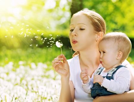 blowing dandelion: Madre e bambina che soffia su un fiore di tarassaco sulla natura in estate nel parco