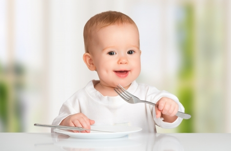 baby cutlery: Funny happy baby with a knife and fork eating food