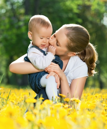 happy family on a walk in the park. mother kissing baby photo