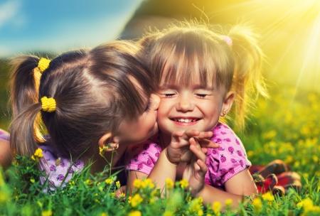 幸せな家族。小さな女の子双子姉妹のキスをし、夏の屋外で笑って