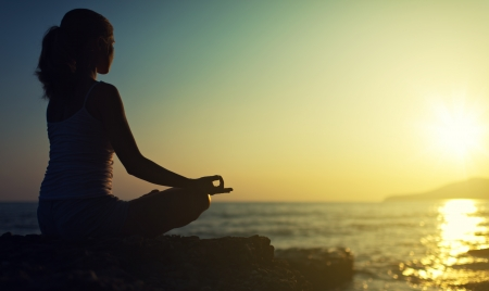 beach yoga: yoga outdoors. silhouette of a woman sitting in a lotus position on the beach at sunset