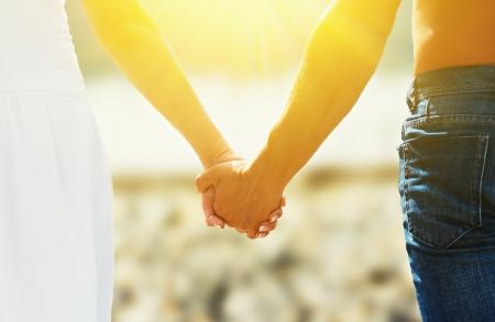愛と家族の概念。ビーチの愛好家の男女の手