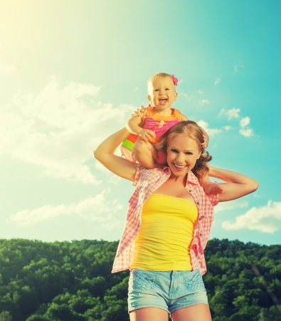 grownups: happy family. mother and daughter baby girl playing on nature outdoors