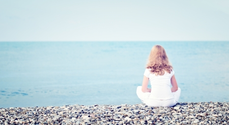 solos: triste solitaria mujer joven y bella en blanco que se sienta de nuevo en la playa de la costa del mar