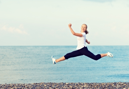 happy young beautiful woman jumping and rejoicing at the beach on the Sea photo