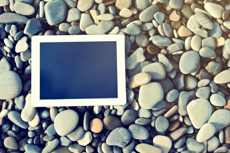 concept of internet and communication. blank empty tablet computer on the beach photo