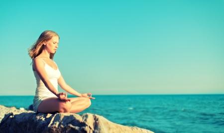 meditating: woman meditating in  lotus yoga on  coast of  sea on the beach Stock Photo