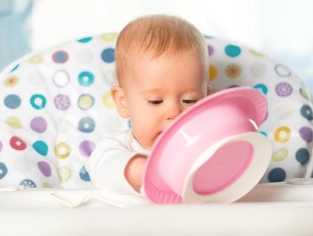 A funny baby is eating from pink plate Stock Photo - 21737754