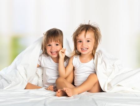 łóżko: Szczęśliwa dziewczynka jest siostrą bliźniaczką w łóżku pod kocem zabawę, uśmiecha