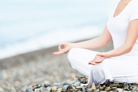 hand of a woman meditating in a yoga pose on the beach photo
