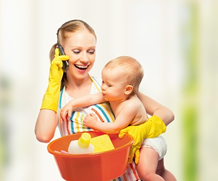 housewife gloves: young happy mother is a housewife with a baby does homework and talking on the phone at home