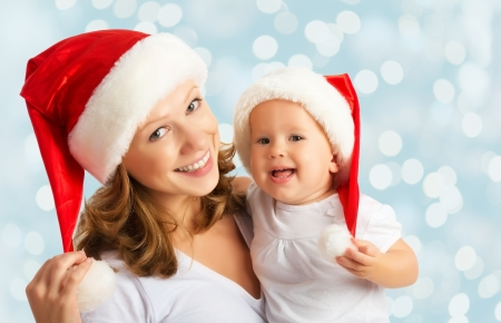 baby christmas: happy family mother and baby in red Christmas hats