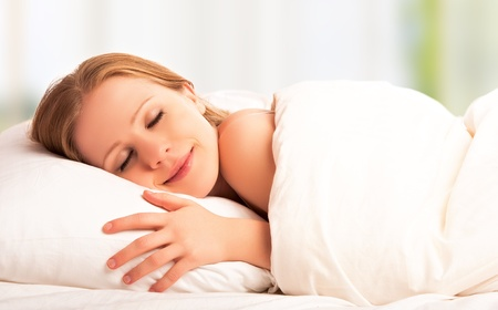 sleeping face: young beautiful woman sleeping and smiles in his sleep in  bed