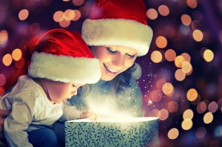 baby kerst: Kerstmagie gift box en een vrouw gelukkig gezin moeder en kind kind Stockfoto