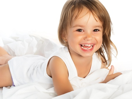 little happy smiling cheerful girl in a white bed isolated photo