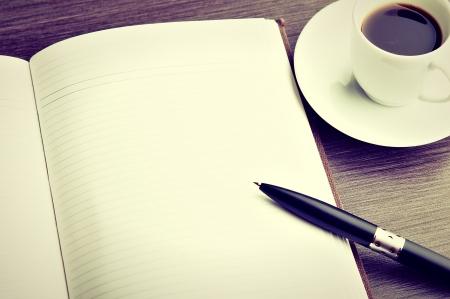 空白の白いノートブック、ペン、机の上のコーヒー カップを開く