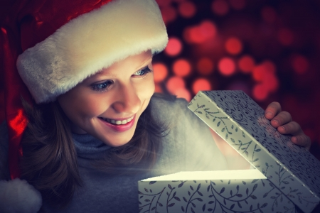 opens: happy woman in a Christmas cap opens the magic box gift