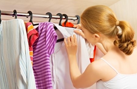 Young woman chooses clothes in the wardrobe closet at home Stock Photo - 22167972