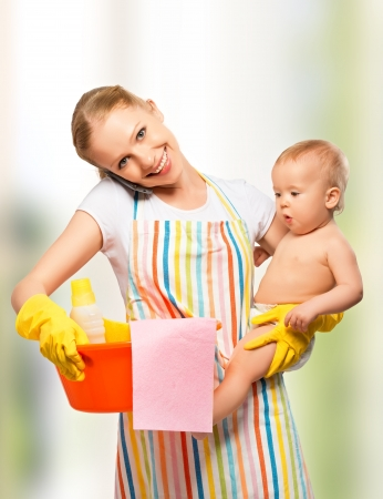 young happy mother is a housewife with a baby does homework and talking on the phone at home photo