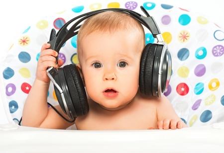 beautiful happy baby with headphones listening to music photo