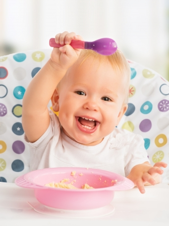 cheerful happy baby child eats itself with a spoon Stock Photo
