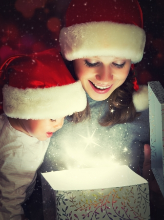xmas baby: Christmas magic gift box and a woman happy family mother and Child baby