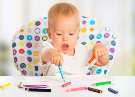 happy baby child draws with colored pencils crayons photo