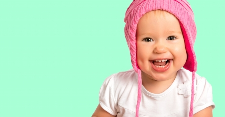 Funny happy baby girl child  in a pink  winter knitted hat laughing photo