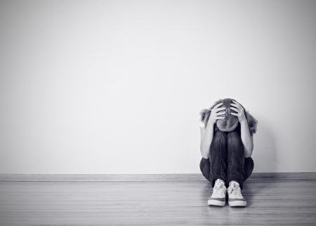 meisje zit in een depressie op de grond bij de muur monochroom