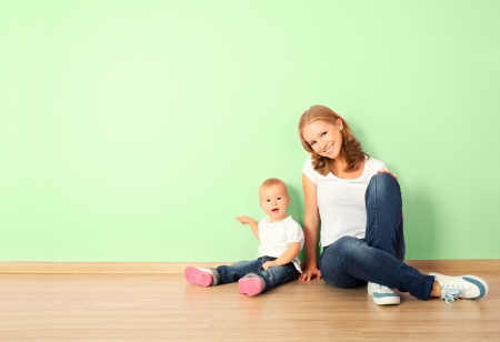 sitting room: happy family of mother and child is a toddler sitting on the floor in an empty home wall in the room