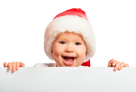 cappello natale: bambino felice in un cappello di Natale e di un cartellone bianco isolato su sfondo bianco