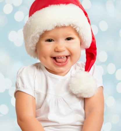 Beautiful funny baby in a Christmas hat  on blue background photo