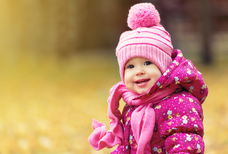 fall fun: happy baby girl child outdoors in the park in autumn on walk Stock Photo